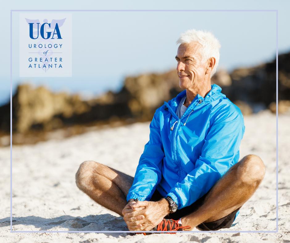 Senior man sitting on a beach enjoying fresh air after his quitting smoking new year's resolution - UGATL