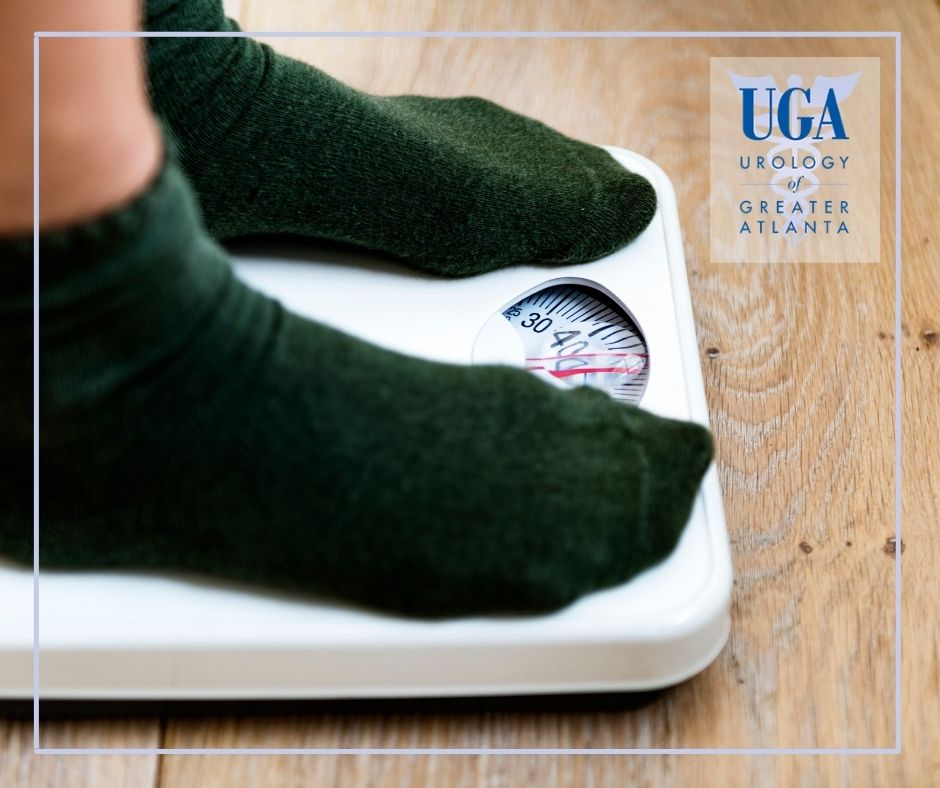 Feet with black socks on a weight scale achieving new year's resolution weight loss goal - UGATL